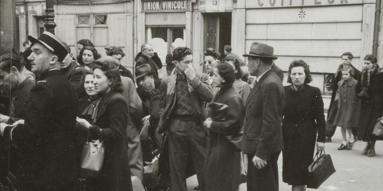 Certains hommes arrivent encore portant leur convocation et sont reçus par les policiers qui gardent l'entrée du gymnase. Des femmes avec enfants arrivent avec des valises et de paquets. Les scènes suivantes montrent qu'elles font la queue et attendent leur tour pour donner les valises.    Le 13 mai 1941, la préfecture de police de Paris adresse 6500 convocations à des hommes juifs étrangers, âgé de 18 à 60 ans, selon les indications contenues dans le fichier du recensement d'octobre 1940.    1061 hommes sont convoqués au gymnase Japy. Plus de 800 se présentent. Un attroupement se forme, encadré par les forces de police déployées en nombre qui contrôlent les abords.