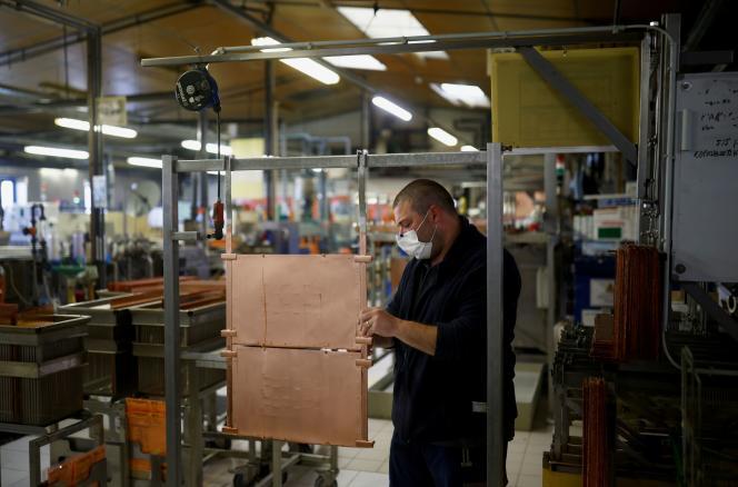 Un salarié d'Atlantec Technologies travaille sur une plaque de cuivre, nécessaire à la fabrication de circuits imprimés, à Malville, près de Nantes, le 11 mai 2021.