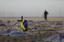 """A Brazilian flag hangs on a cross amid mock body bags on Copacabana beach placed by the NGO """"Rio de Paz"""" in memory of the 400,000 victims of COVID-19 nationwide in Brazil, in Rio de Janeiro, Brazil, Friday, April 30, 2021. (AP Photo/Silvia Izquierdo)"""