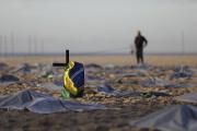 Un drapeau brésilien sur une croix installée sur la plage de Copacabana en hommage aux victimes du Covid-19, à Rio de Janeiro, le 30 avril 2021.