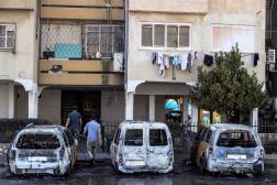 Des passants devant des voitures incendiées à Lod, le 12 mai 2021.