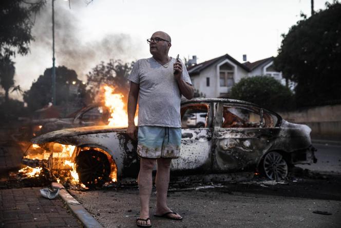 عابری در مقابل یک ماشین سوخته هنگام آشوب در لود ، در حومه تل آویو ، در 11 مه 2021.
