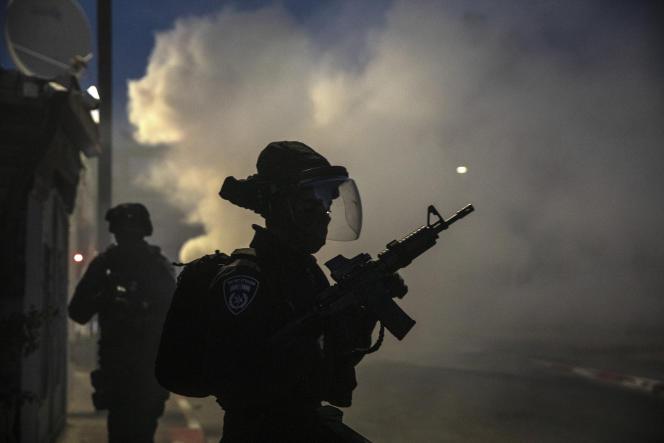 Les forces israéliennes courent lors d'affrontements avec des Arabes israéliens dans la ville mixte israélienne de Lod, en Israël, le mardi 11 mai 2021.