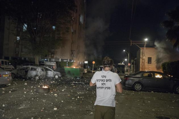 Des colons et des militants juifs, souvent armés, jettent des pierres sur les habitations de Palestiniens. Sur le T-shirt de l'un d'eux : « Le Golan combat l'ennemi mais n'expulse pas les juifs. » Lod, Israël, le 12 mai 2021.