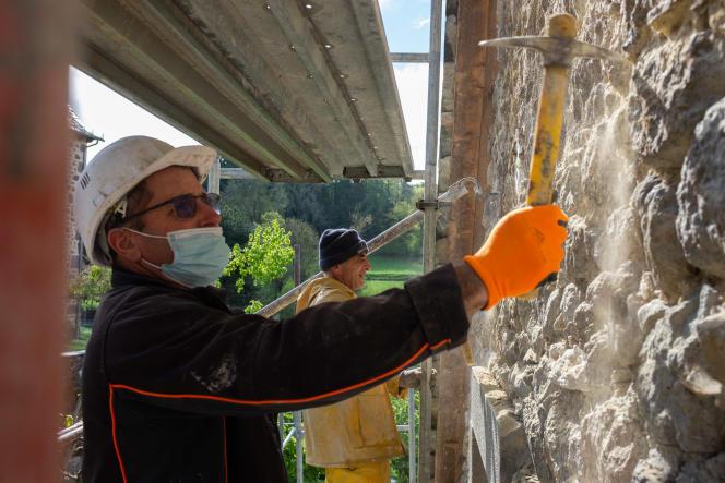 Le maçon Rémi Crétois travaille avec son coéquipier sur un chantier de rénovation près d'Aurillac (Cantal), le 7mai 2021.