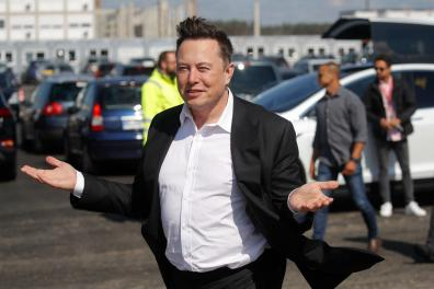"""(FILES) In this file photo taken on September 03, 2020 Tesla CEO Elon Musk gestures as he arrives to visit the construction site of the future US electric car giant Tesla, in Gruenheide near Berlin. Carmaker Tesla's """"gigafactory"""" near Berlin will not open in July as planned due to changes in the building permit application, the region said on April 27, without giving a new date. / AFP / Odd ANDERSEN"""