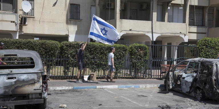 Lod, Israël, le 12 mai 2021  Un petit groupe de colons juifs, dont au moins l'un d'entre eux a fait le voyage depuis le Golan, défile, drapeaux en main, dans le centre ancien de Lod. Un quartier aux communautés défavorisées et mixtes, était habité par des palestiniens d'Israël, avant que des colons qui s'y installent après le démantèlement des colonies de Gaza en 2005.  Photo Laurent Van der Stockt pour Le Monde