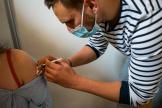 Julien Hellet, 27 ans, infirmier libéral, vaccine une jeune femme. Centre de vaccination de la mairie du 18e, Paris le 11 mai 2021.