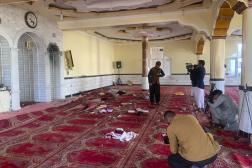 Des journalistes prennent en photo des débris après une explosion mortelle dans une mosquée, près de Kaboul en Afghanistan, le 14mai 2021.