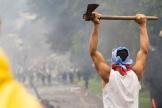 Un manifestant armé d'une hâche face à des policiers dans la ville dePopayán, le 14 mai en Colombie.