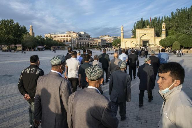 Des Ouïgours se rendent à la mosquée d'Id Kah pour la prière de l'Aïd-el-Fitr, sous l'œil d'un agent de sécurité àKachgar, le 13 avril.