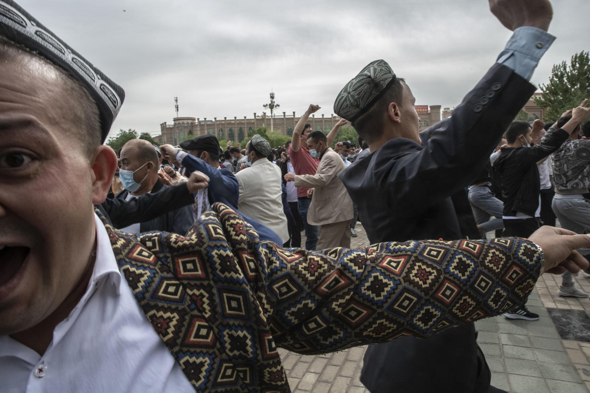 Devant la mosquée Id Kah le jour de l'Aïd el-Fitr, une foule de Ouïgours danse pour célébrer la fin du ramadan, à Kachgar, le 13 mai 2021.