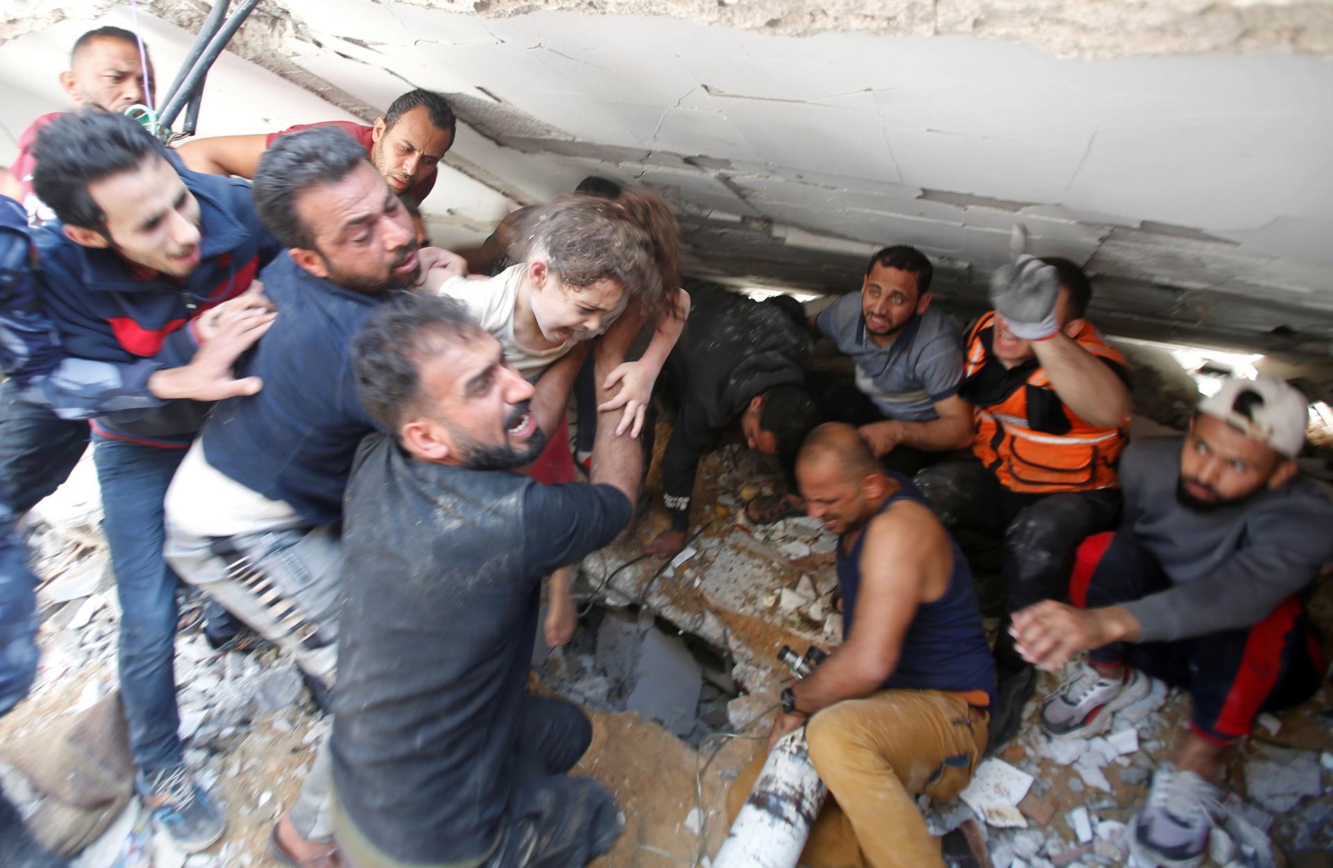 Les sauveteurs portent une fille alors qu'ils recherchent des victimes parmi les décombres sur le site des frappes aériennes israéliennes, dans la ville de Gaza, le 16 mai 2021.