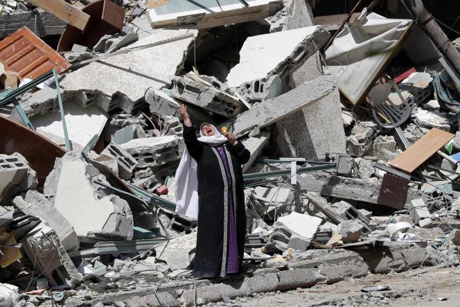 Une femme devant les ruines d'un immeuble détruit lors de l'attaque aérienne israélienne à Gaza, le 16 mai 2021.