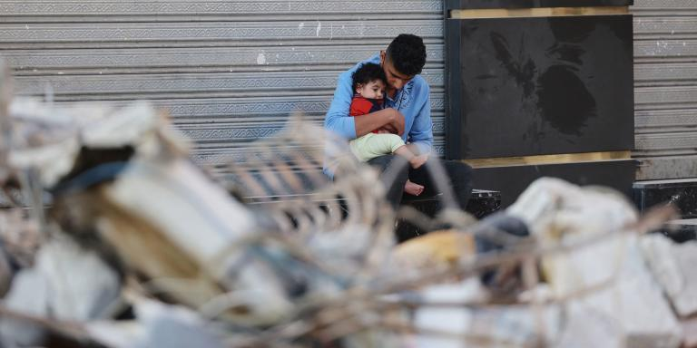 A Palestinian man holds his son as he sits outside a closed shop in front of his destroyed home in a residential neighbourhood in Gaza City early on May 16, 2021, following massive Israeli bombardment of the Hamas-controlled enclave. The previous day, an Israeli air strike flattened a 13-floor building housing Qatar-based Al Jazeera television and the US news agency the Associated Press in the Gaza Strip.  / AFP / MOHAMMED ABED