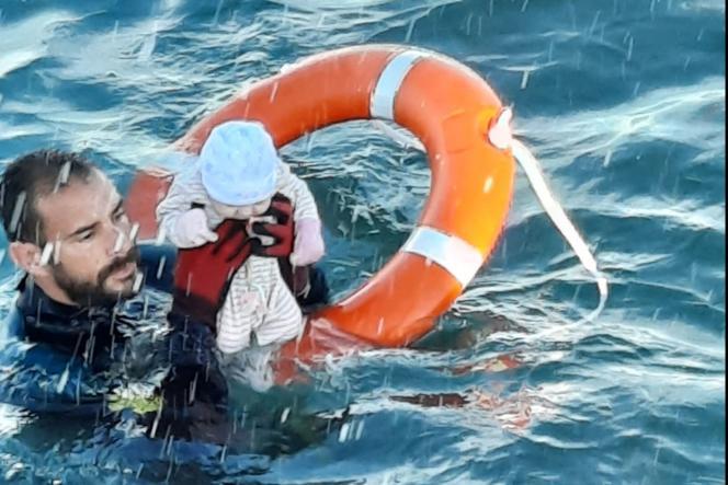 Image fournie le 18 mai 2021 par la garde civile espagnole montrantJuan Francisco Valle, un plongeur du groupe spécial pour les activités sous-marines sauvant un nourrison des eaux de la Méditerranée.