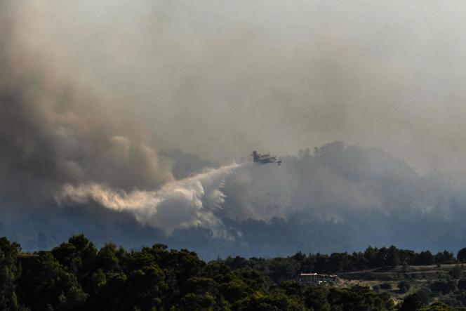 Ένα πυροσβεστικό αεροπλάνο ρίχνει νερό σε δασικές πυρκαγιές κοντά στο χωριό Αλεποχώρι, Ελλάδα, 20 Μαΐου 2021.