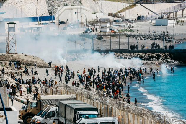 Οι ισπανικές δυνάμεις ασφαλείας πυροδοτούν δάκρυ αέριο σε Μαροκινούς και υποσαχάρια μετανάστες στο Fnideq στις 19 Μαΐου 2021.