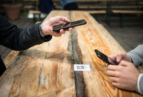 """Two guests register by scanning a QR code with their mobile phones in a beer garden in Berlin on May 21, 2021, as many cities and regions were lifting restrictions over the Pentecost holiday weekend, amid the ongoing novel coronavirus / COVID-19 pandemic. Many Germans were able to visit a beer garden, dine outdoors or go swimming for the first time in months. Germany has been in some form of virus shutdown since November and tentative reopenings in March were quickly quashed by national """"emergency brake"""" measures to stop a spiralling third wave of the virus. / AFP / Stefanie LOOS"""