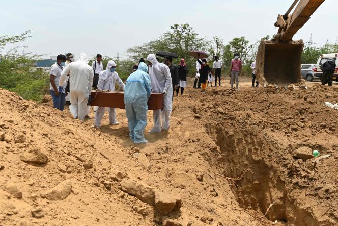 Hulpdiensten begraven een Covid-19-slachtoffer in een dorp in de buurt van Faridabad.