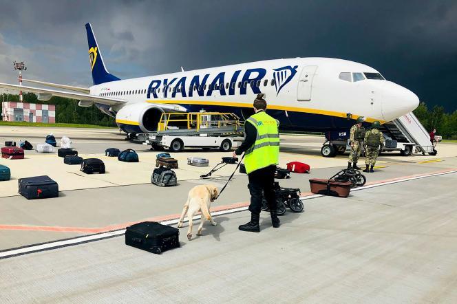 Un maître-chien contrôle les bagages du Boeing 737-8AS de Ryanair, à l'aéroport international de Minsk, en Biélorussie, le 23 mai 2021.