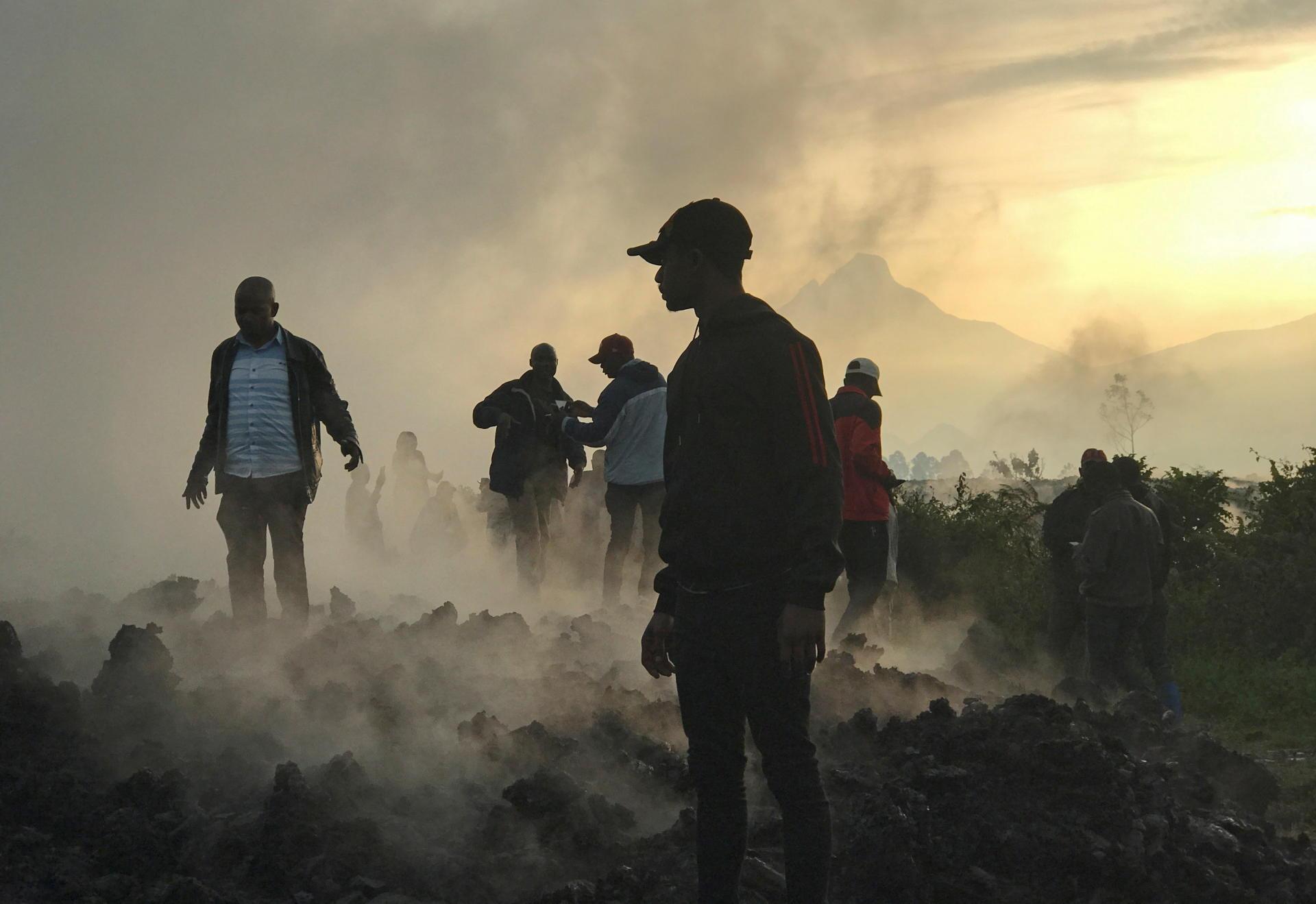 Des habitants marchent près de maisons détruites par la lave fumante déposée par l'éruption du volcan du Mont Nyiragongo près de Goma, en République démocratique du Congo, le 23 mai 2021.