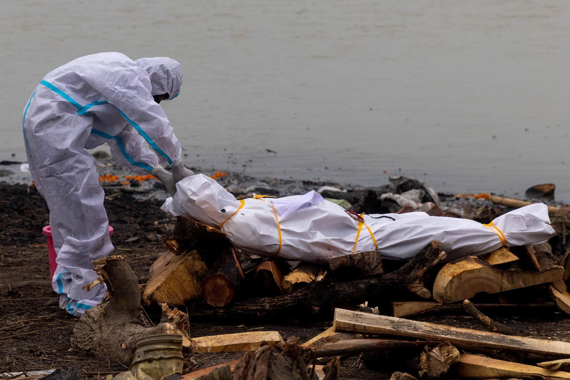 Un homme vêtu d'une combinaison de protection porte le corps d'un membre de sa famille, décédé des suites du Covid-19, avant son incinération sur les rives du Gange, à Garhmukteshwar (Uttar Pradesh), le 6 mai 2021.