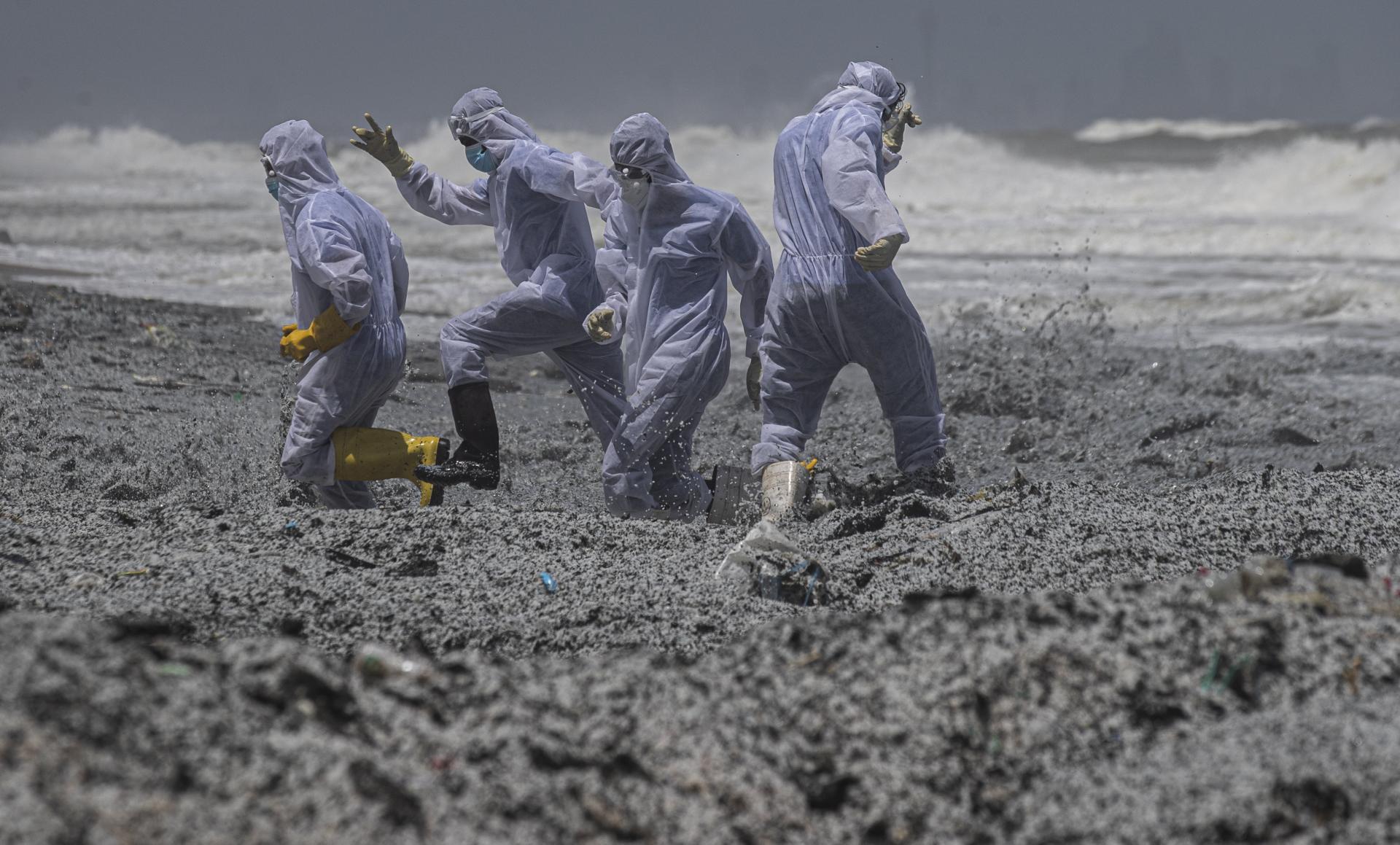 Des soldats de la marine sri-lankaise en tenue de protection sur la plage de Kapungoda, polluée par la cargaison du porte-conteneurs incendié au large du Sri Lanka, le 27 mai 2021.