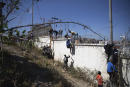 People climb a fence in the area at the border of Morocco and Spain, outside the Spanish enclave of Ceuta, Tuesday, May 18, 2021. (AP Photo/Mosa'ab Elshamy)