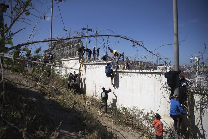 Des personnes escaladent un mur barbelé, dans la zone frontalière entre le Maroc et l'Espagne, le 18 mai 2021.
