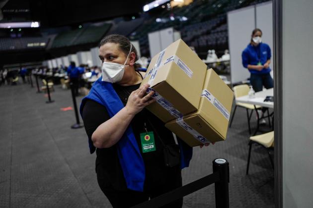 Une organisatrice transporte des cartons de tests dans la hall de l'AccorHotels Arena, à Paris, le 26 mai 2021.