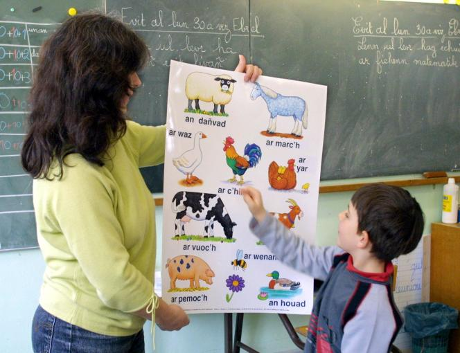A pupil works with his teacher, in a class of the Diwan bilingual school in Brest (Finistère), on May 2, 2001.