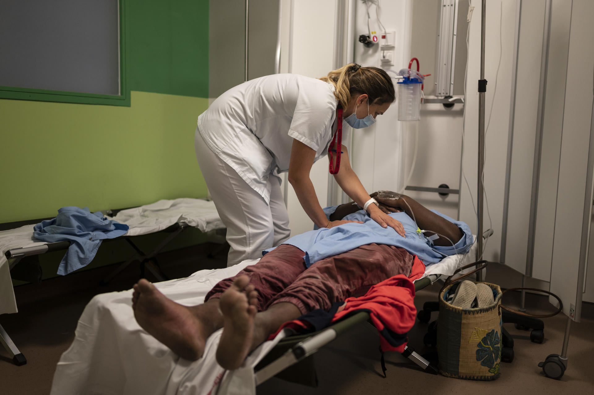 Een spoedarts onderzoekt een patiënt op noodbrancards van hetzelfde type als in het leger.  CHOR, Saint Paul, Réunion, 25 mei 2021.