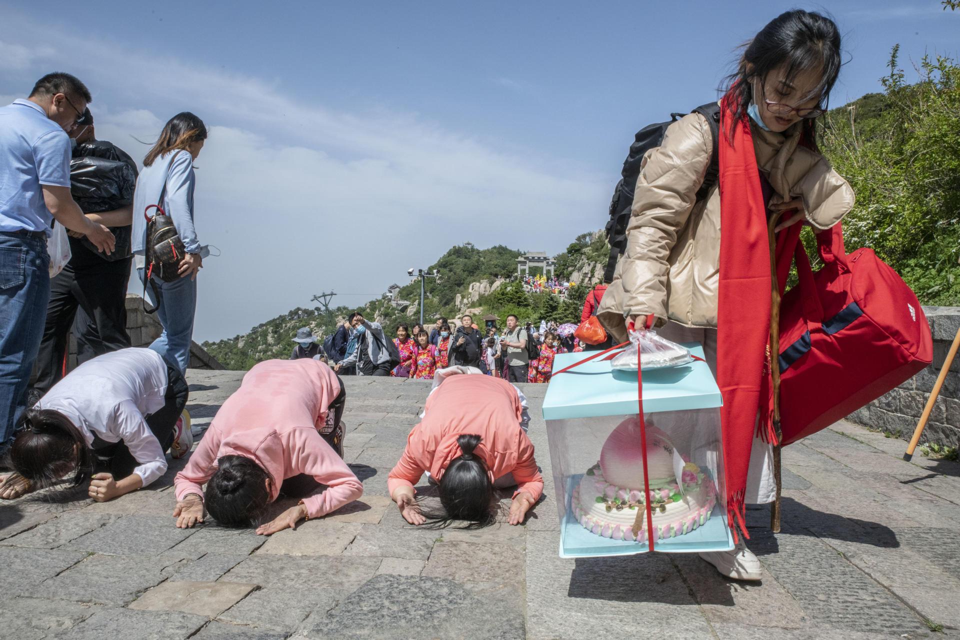 Une femme apporte en offrande un gâteau en forme de pêche, symbole d'éternité.