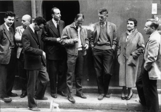 De gauche à droite : Alain Robbe-Grillet, Claude Simon, Claude Mauriac, Jérôme Lindon, Robert Pinget, Samuel Beckett, Nathalie Sarraute et Claude Ollier devant les Editions de Minuit, à Paris, en 1959.