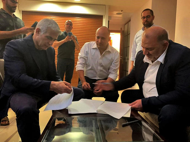 A photo provided by the United Arab Emirates Ram on June 2, 2021, shows Ram Mansour Abbas, leader of the Arab-Israeli Islamic Conservative Party, signing a coalition agreement with Israeli opposition leader Jair Lapid (left) and a right-wing nationalist.  Naphtali Bennett, a technology millionaire in Ramadhan, near the coastal city of Tel Aviv.