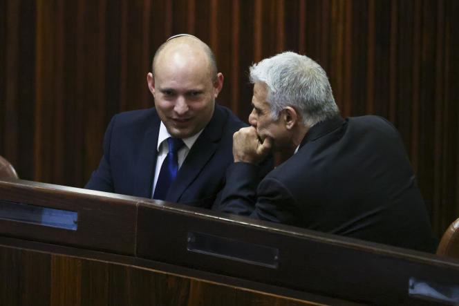 Yamina party leader Naphtali Bennett, left, and Yesh Adidas leader Yair Lapid in a special Knesset session, Israeli lawmakers elect a new president, at the Knesset meeting in Jerusalem on June 2, 2021.