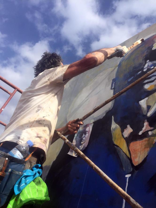 L'artiste plasticien Bruce Clarke travaille sur une fresque des« Hommes debout», dans le «Jardin de la mémoire» à Kigali, en juin 2021.