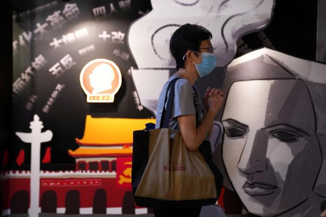 Un visiteur prie à côté d'un tableau représentant la déesse de la démocratie au Musée du 4-Juin lors de sa réouverture à Hongkong, le 30 mai.