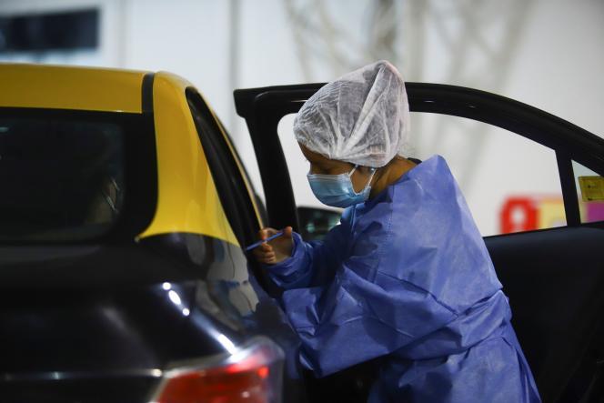 Un agent de santé administre une dose du vaccin d'AstraZeneca dans un drive-in, à Buenos Aires, le 4 juin 2021.
