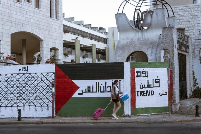 Une adolescente citoyenne palestinienne d'Israël (portant son sac au retour d'une sortie scolaire) passe devant des graffitis «La Palestine n'est pas une mode» et «L'heure de la victoire a sonné». Le 2 juin 2021, à Nazareth (Israël).