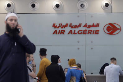Passengers wait to check in at an Air Algeria counter for a flight to Paris at Algiers' Houari Boumediene Airport on June 1, 2021, after Algeria reopened its borders following a 15-months closure due to the Covid-19 pandemic. - Algeria has slightly relaxed the conditions for entry to its soil of its nationals stranded abroad due to the Covid-19 epidemic, by reducing the costs of compulsory confinement, a statement from the Council of Ministers said. (Photo by - / AFP)