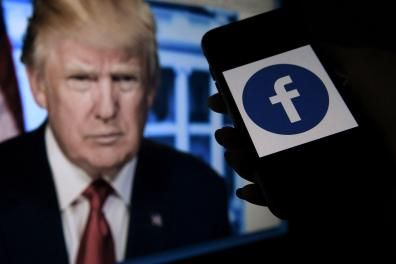 (FILES) In this file photo illustration taken on May 04, 2021, a phone screen displays a Facebook logo with the official portrait of former US President Donald Trump on the background in Arlington, Virginia. Facebook on June 4, 2021, banned former US President Donald Trump for two years, saying he deserved the maximum punishment for violating its rules over a deadly attack by his supporters on the US Capitol. - / AFP / Olivier DOULIERY