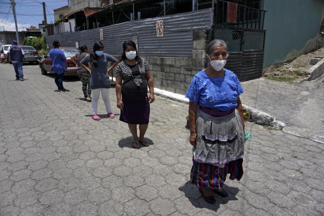 Des femmes affectées financièrement par la pandémie font la queue pour recevoir un repas chaud le 24 juillet 2020 au Guatemala.