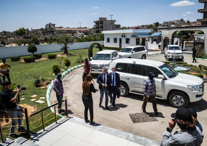 Członkowie kurdyjskich sił bezpieczeństwa stoją na straży przybycia holenderskiej delegacji dyplomatycznej, na czele której stoi holenderski specjalny wysłannik do Syrii Emil de Bont (z lewej) i dyrektor ds. konsularnych w holenderskim ministerstwie spraw zagranicznych Dirk Jan Nieuwenhuis (z prawej). ), która jest przekazywana krewnym bojowników Państwa Islamskiego w mieście Kamiszli w północno-wschodniej Syrii 5 czerwca 2021 r.