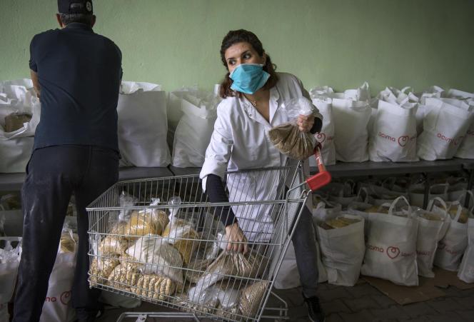 Des bénévoles marocains de l'organisation locale Institut national de solidarité avec les femmes en détresse préparent des dons alimentaires qui seront distribués à Casablanca le 8 avril 2020 pendant la pandémie de coronavirus Covid-19.