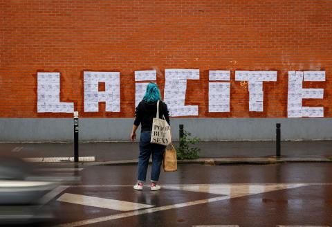 """A feminist activist looks at posters of a drawing by French cartoonist Charb to read """" Laicite """" in Montreuil, on October 20, 2020. - Feminist activists were arrested on October 19, 2020 in Toulouse as they were carrying out during a similar action after a teacher was beheaded for showing pupils cartoons of the Prophet Mohammed. His murder in a Paris suburb on October 16 shocked the country and brought back memories of a wave of Islamist violence in 2015. (Photo by - / AFP)"""