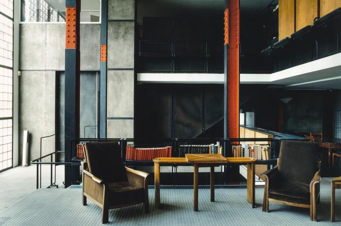 Le grand hall de la Maison de verre et ses colonnes boulonnées. On y distingue le fauteuil MF219 et le bureau MT876, dessinés par Pierre Chareau.