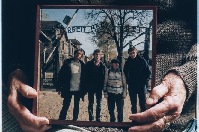 Ginette Kolinka tient la photo prise lors de son voyage en famille à Birkenau, avec Richard, Mathis et Roman, en Pologne,en novembre 2013.