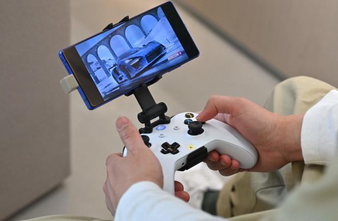 Un employé de Microsoft joue sur un smartphone en utilisant une manette Xbox, à Séoul en 2020